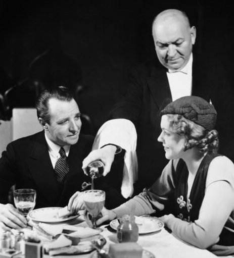vintage waiter pouring drink at a restaurant
