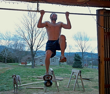 man doing pull-up with kettlebell on foot