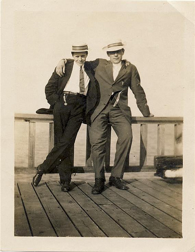 Vintage friends in suits wearing hats standing on sea site.