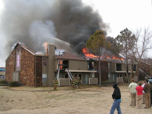 firefighters working on burning apartment complex