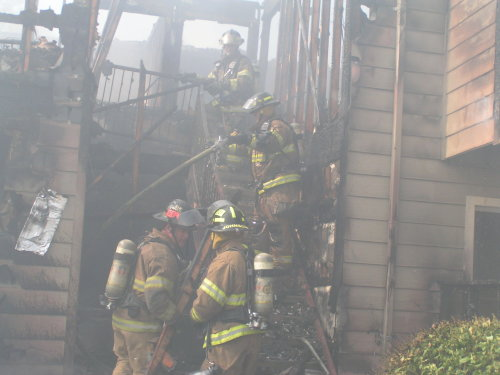 firemen crew working on burning house smoking