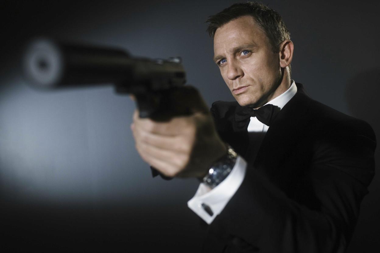 Daniel Craig give posing with gun.