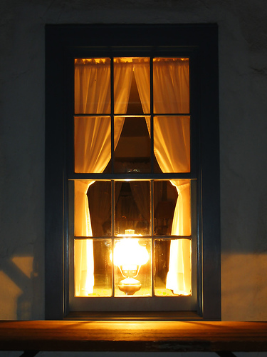 vintage lamp burning in window