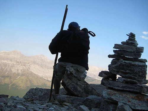 hiker on top of mountain cairn rite of passage