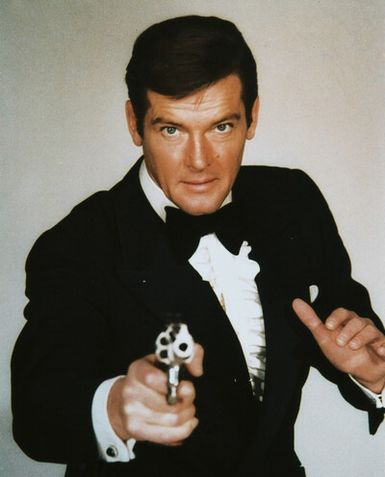 roger moore james bond posing in suit gun