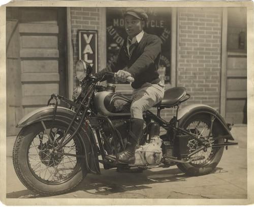 Vintage man sitting on motorcycle.