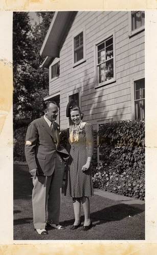 Vintage husband and wife standing in driveway.