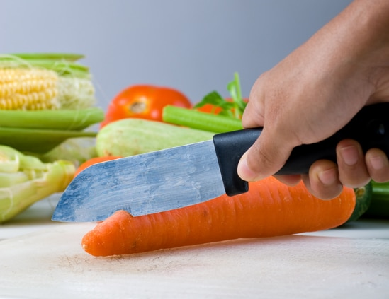 cutting carrot with kitchen knife vegetables