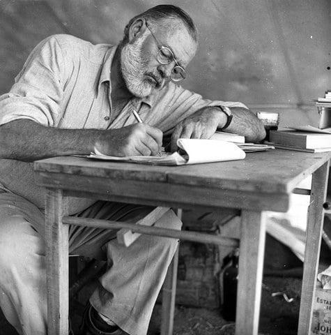 Vintage Ernest Hemingway writing at desk.