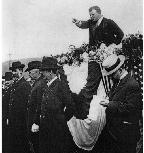 Theodore Roosevelt pointing and giving speech in public.