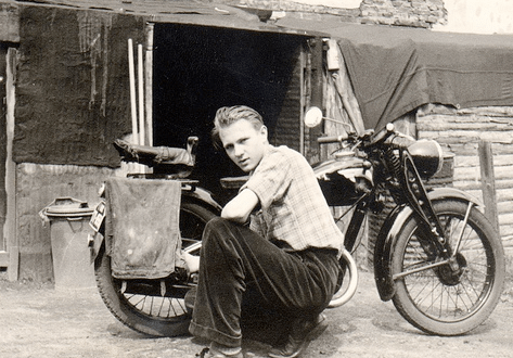 Vintage man giving pose with motorcycle.