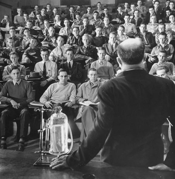 Vintage professor giving lecture to classroom students.