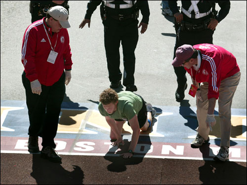 A man crawling in boston marathon to finish line across the team.