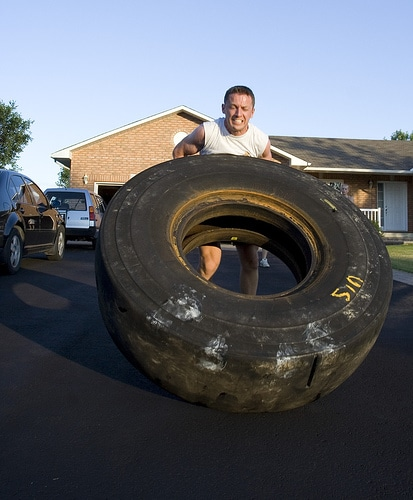 man flipping tractor tire driveway diy workout