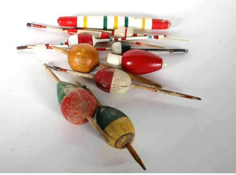 Collection of wood and plastic fishing bobbers.