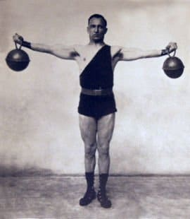 Vintage man holding kettlebells in both hands.
