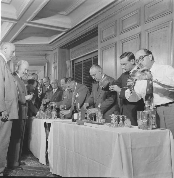 Vintage men making martinis cocktails placed on the table.