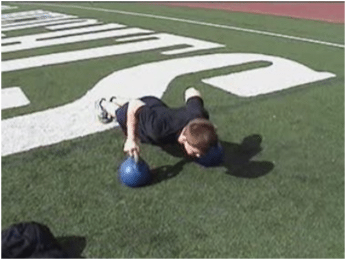 Man doing kettlebell push up in the ground.