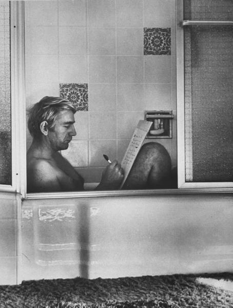 Vintage man writing on paper in the bathtub.