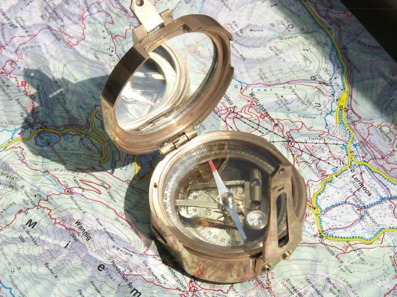 vintage compass Minolta DSC lying on map