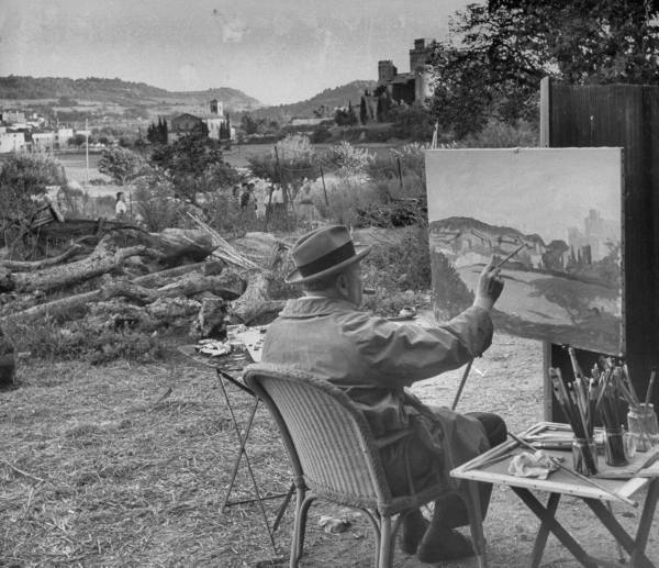 Winston Churchill hobby painting outside with cigar.