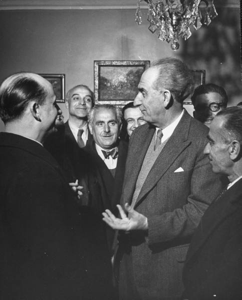 Gathering of men in party commanding a room and talking.