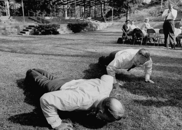 Two vintage old businessmen doing push-ups.