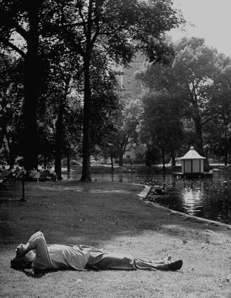 Vintage man lying on grass in the park near the lake.
