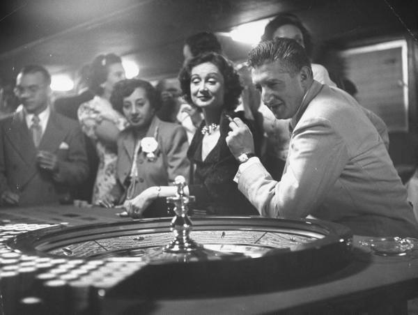 Vintage men playing roulette game in casino.