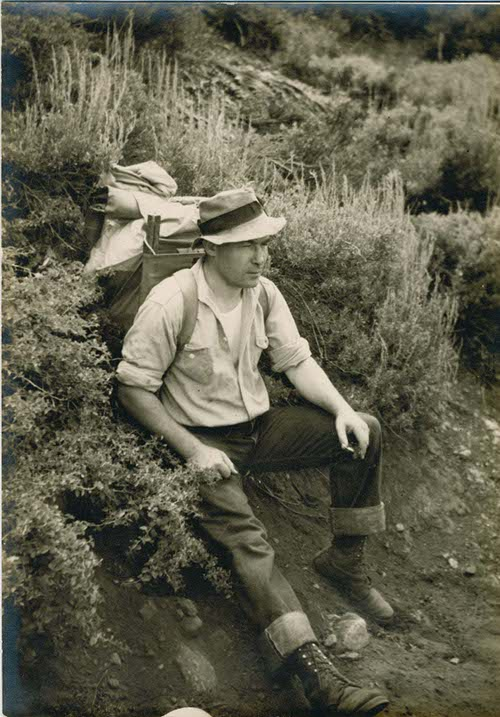 Vintage man wearing backpack while sitting in the brushes.