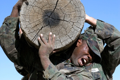 Navy seals training while carrying heavy log on his shoulder.