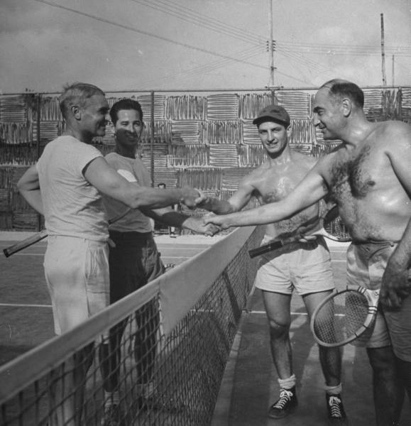 Vintage tennis players shaking hands in the playing area.