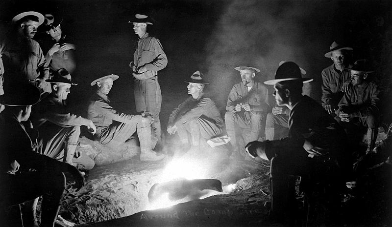 Vintage cowboys sitting around the campfire.