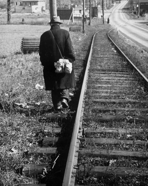 Hobo Vagabond wearing trench coat and walking along with railway track.