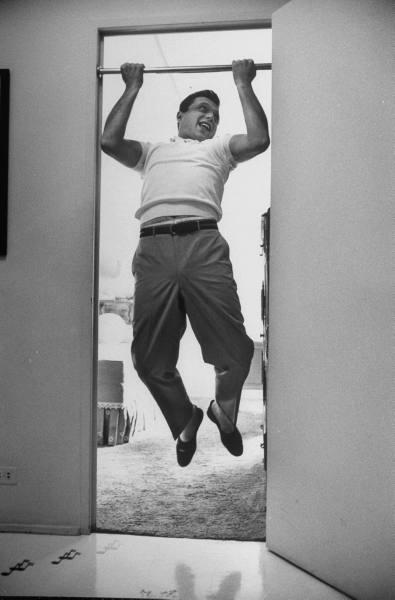 Vintage man enjoying while doing pull ups in doorway.