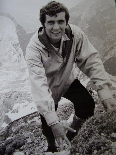 Vintage man posing while climbing on the rock.