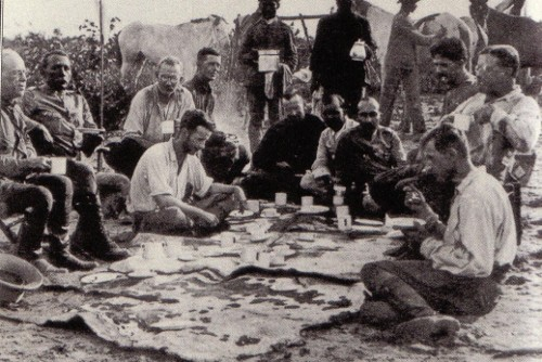 Teddy Roosevelt taking tea with people while sitting on the ground.