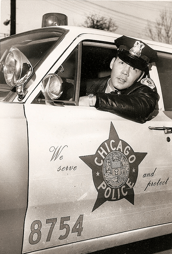 Vintage Chicago police officer looking out from his car's window.