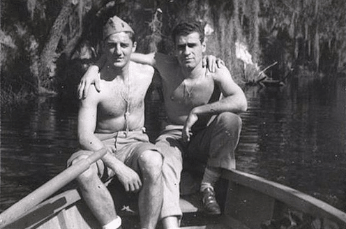Two vintage shirtless friends posing together in boat on a lake.
