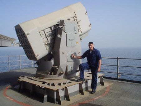 Dan Smith giving pose and standing with US Navy sailor warship.