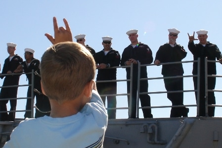 young boy waving to navy sailors shipping out