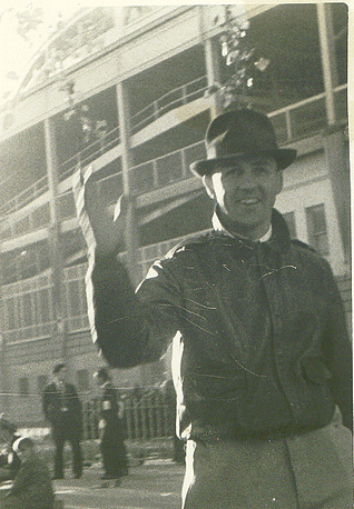 Vintage man waving in front of camera.
