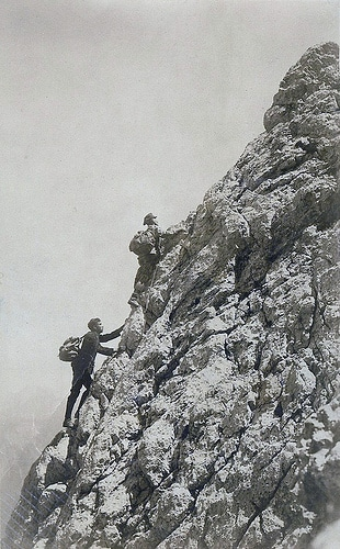 Vintage mountain climbing men scaling rock.