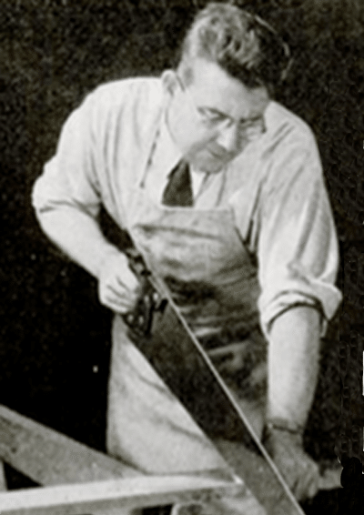 Vintage man using a handsaw for cutting wood.