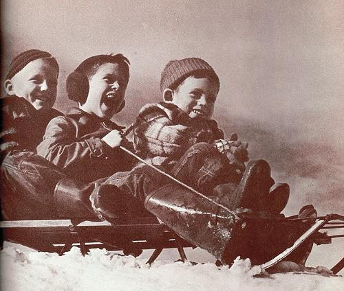 Vintage boys sledding in snow.