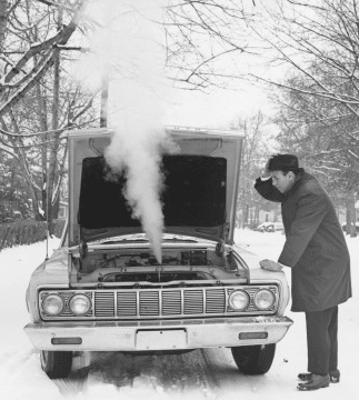vintage Broken down car winter snow steam from engine