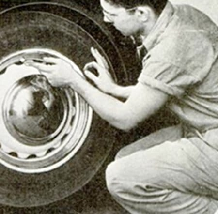 vintage man working on auto car tire