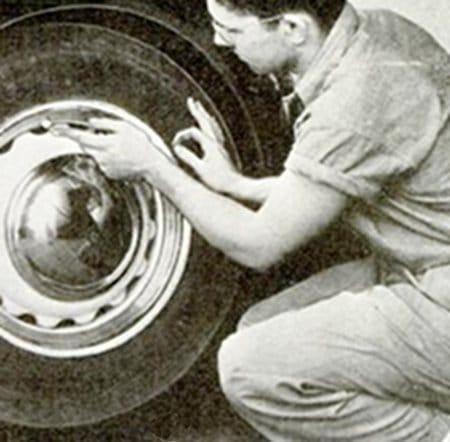 Vintage man working on car tire.