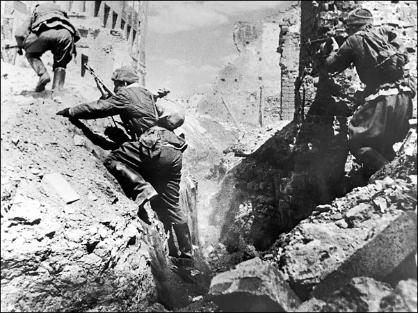 Soldiers climbing up the rocks in a ruined city.