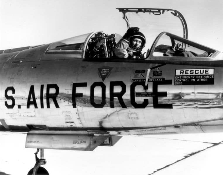 Vintage Chuck Yeager waving while sitting in cockpit.